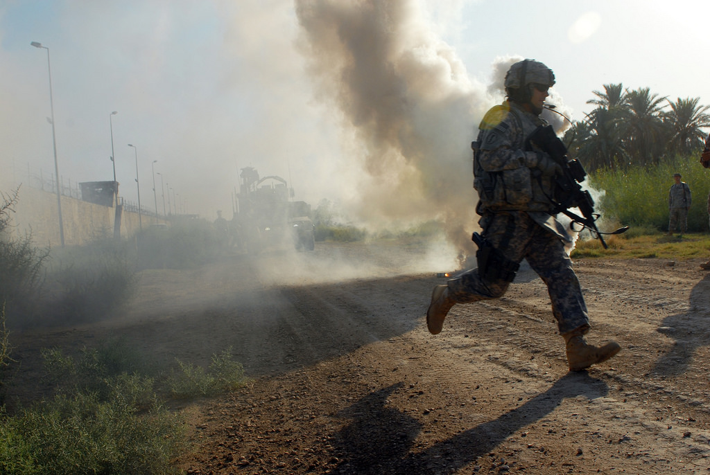 After popping a smoke grenade to signal where medevac helicopters should land, Sgt. James Wendling, a team leader from Mansfield, Ohio, assigned to D Troop, Division Special Troops Battalion, 1st Cavalry Division, runs to re-assure a simulated casualty during training at Camp Slayer, Baghdad, Sept. 22. The DSTB Soldiers, who are frequently outside the wire, were offered an opportunity to hone their skills by running through two different combat scenarios with their squads.
